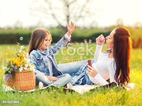 507271044istockphoto Happy mother and daughter blowing bubbles in the park 641637654