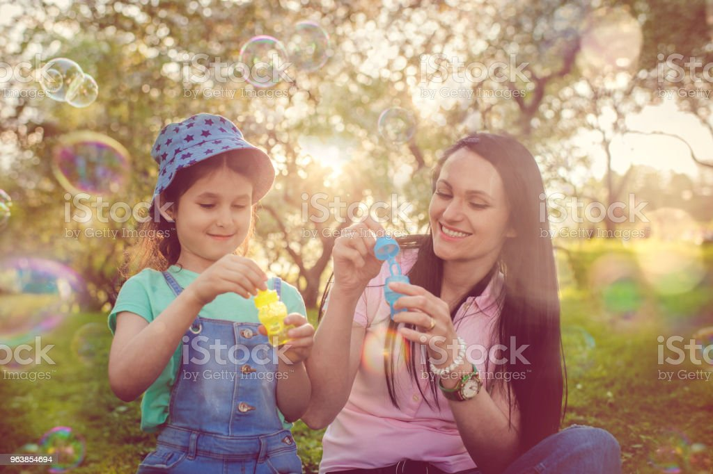 Happy mother and daughter blowing bubbles in the park - Royalty-free 6-7 Years Stock Photo