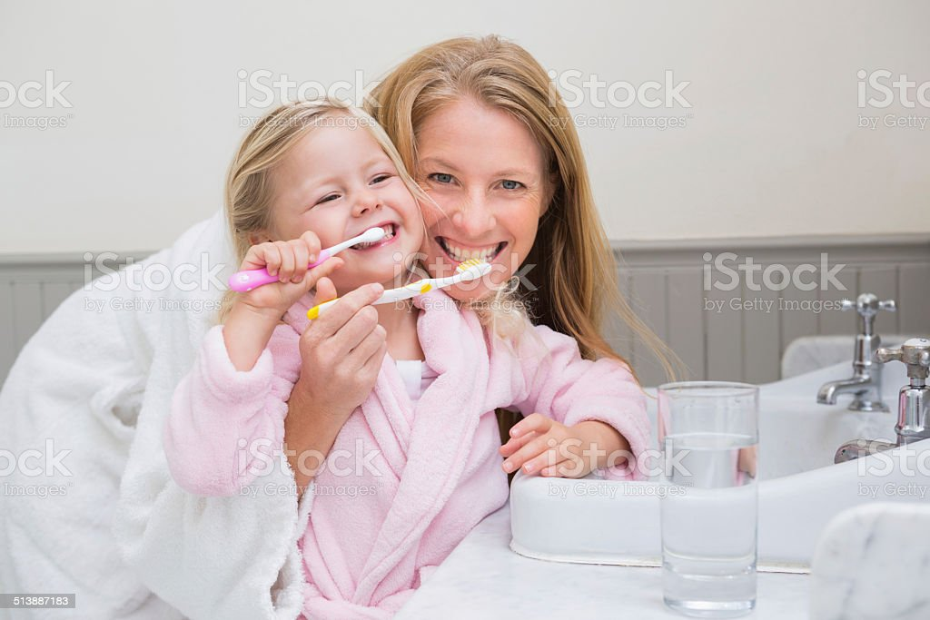 Happy mother and daughter brushing their teeth stock photo