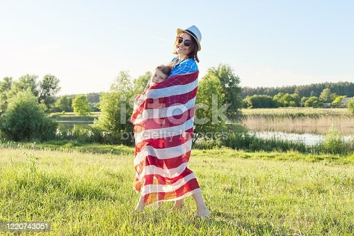 539482224 istock photo Happy mother and daughter child girl hugging under the American flag 1220743051