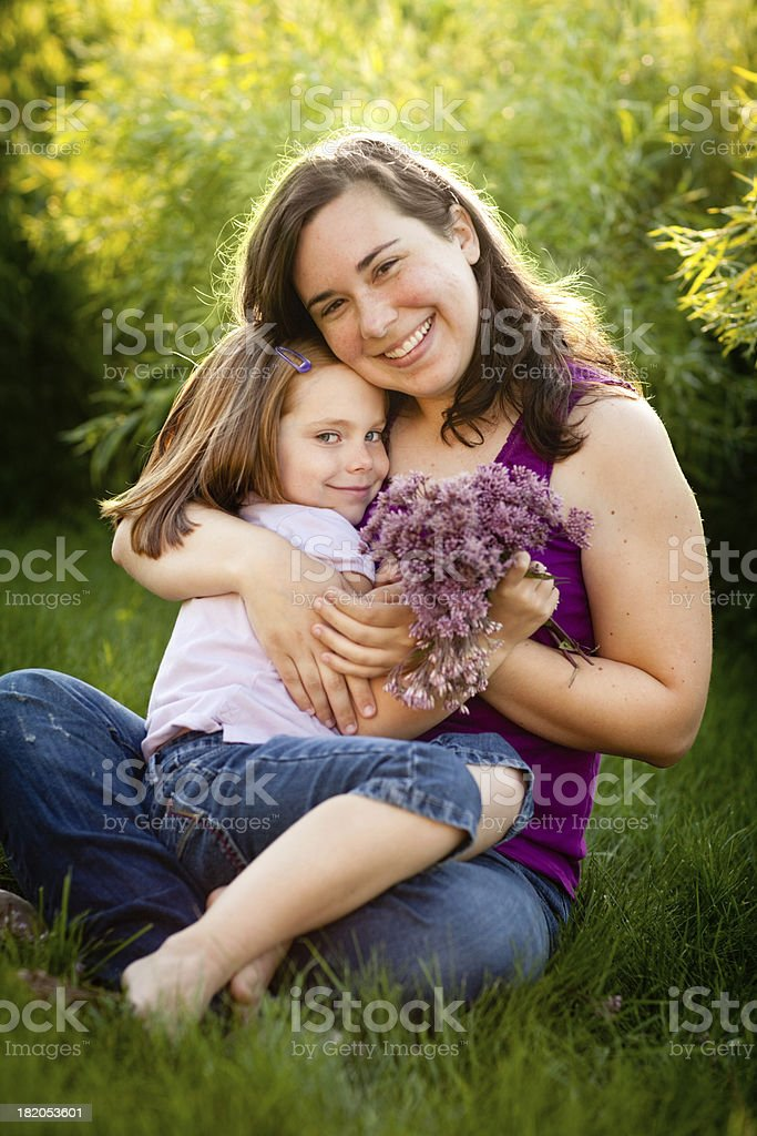 Happy Mother and Daughter Cuddling Together Outside royalty-free stock photo