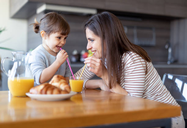 Happy mother and daughter drinking juice together stock photo