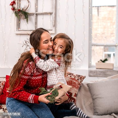 1061876006 istock photo Happy mother and daughter embrace holding gifts. 1075873826