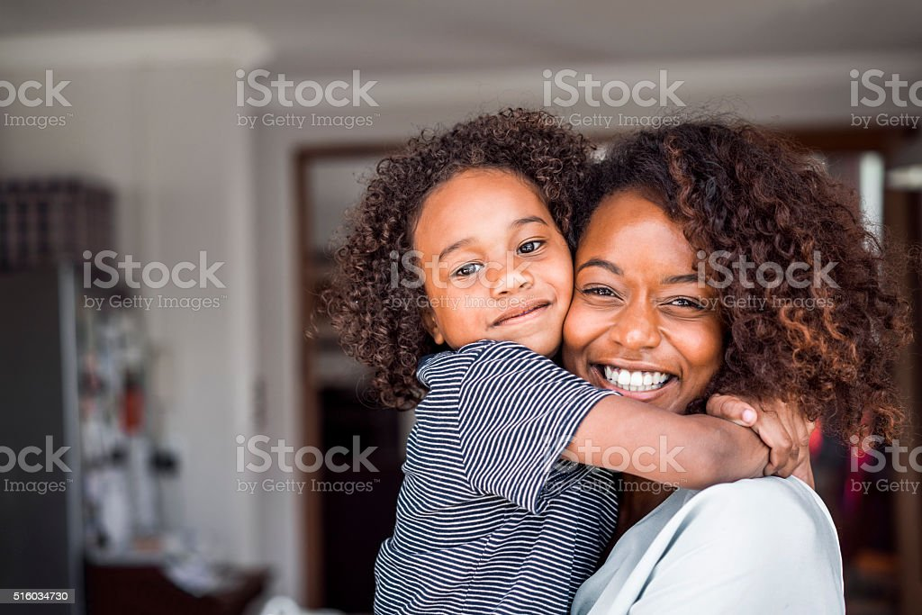 Happy mother and daughter embracing at home stock photo