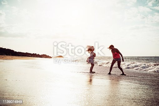 Happy mother and daughter having fun on tropical beach at sunset - Family playing next see during summer vacation - Concept of parent, love and happiness