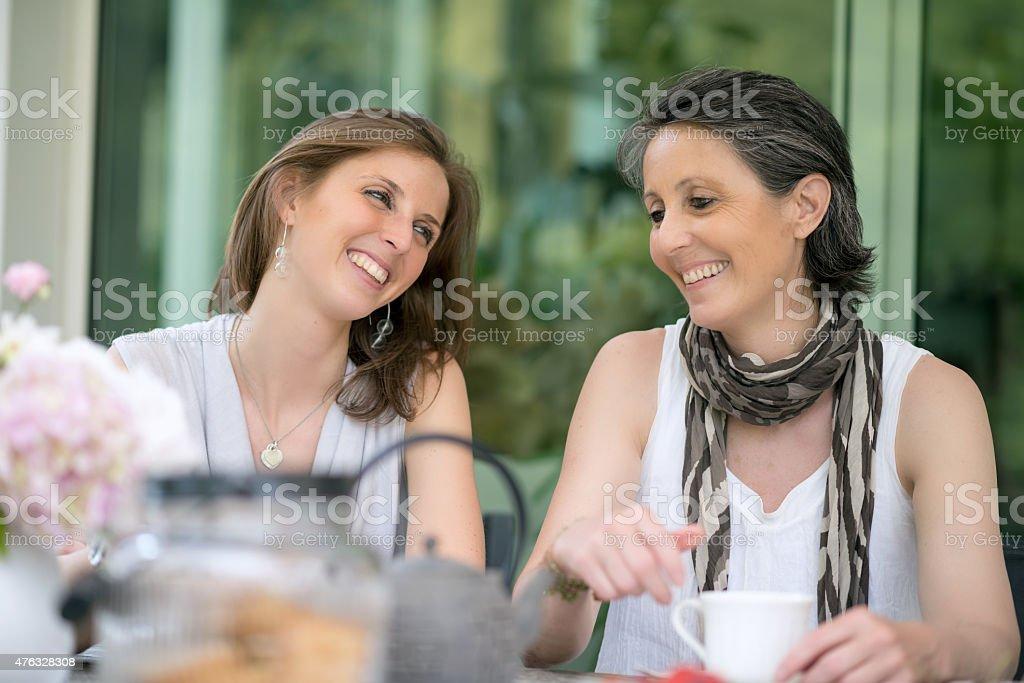 Happy mother and daughter having tea outdoor stock photo