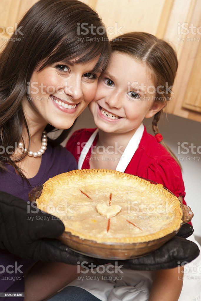 Happy Mother and Daughter Holding Cherry Pie in Kitchen royalty-free stock photo