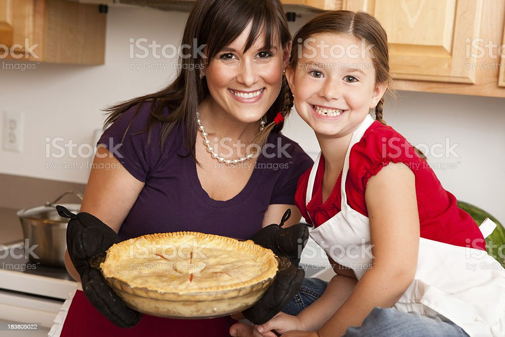 Happy Mother and Daughter Holding Homemade Pie in Kitchen stock photo