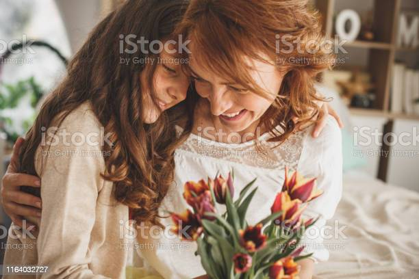 Happy mother and daughter hugging and holding a bouquet of fresh picture id1164032727?b=1&k=6&m=1164032727&s=612x612&h= zj75ksjckdfjpcl0yrttbwf0uly7yhoafpnn70xxju=