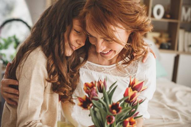 Glückliche Mutter und Tochter umarmen und halten einen Strauß von frischen Blumen – Foto