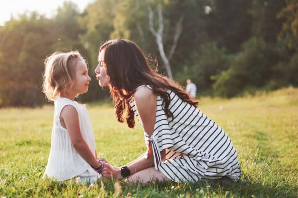 Glückliche Mutter und Tochter umarmten sich in einem Park in der Sonne auf einem strahlenden sommerlichen Hintergrund von Kräutern. – Foto