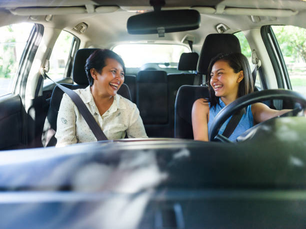 Happy mother and daughter in a car stock photo