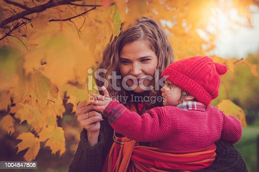 istock Happy mother and daughter in autumn park 1004847808