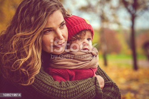 istock Happy mother and daughter in autumn park 1035219514