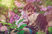 Happy mother and daughter enjoying summer among blooming lilacs