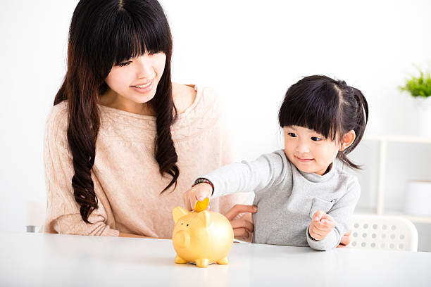 Happy mother and daughter Inserting Coin In Piggy bank stock photo