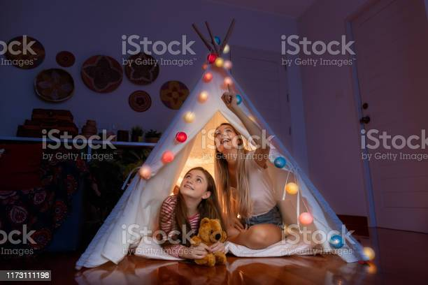 Photo of Happy mother and daughter inside tepee tent in bedroom, looking and pointing ceiling counting stars; family relationship concept.