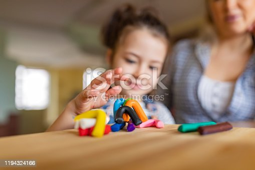 A young single mother and her beautiful little daughter are sitting at the table in a domestic room and making sculptures with a colorful child's play clay.
