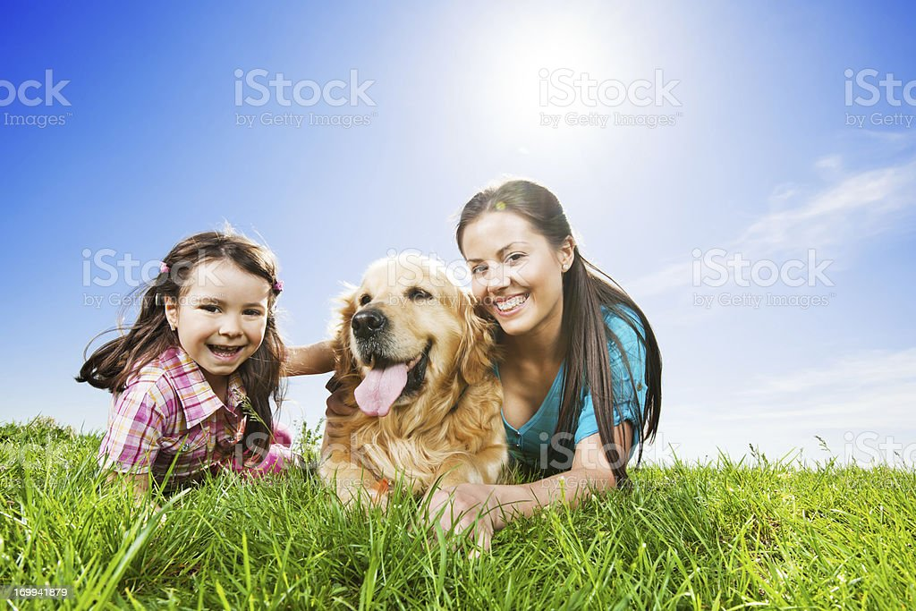 Happy mother and daughter lying in  park with their dog. royalty-free stock photo