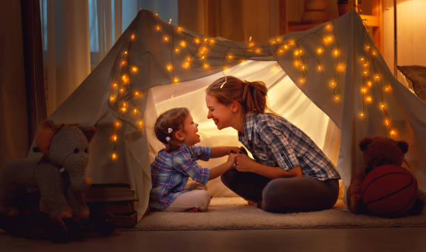 happy mother and daughter playing at home in tent stock photo