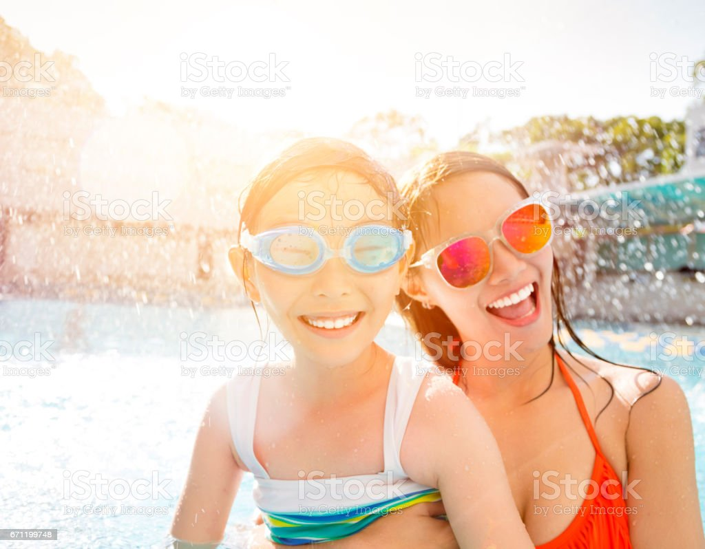 Happy mother and daughter playing in swimming pool stock photo