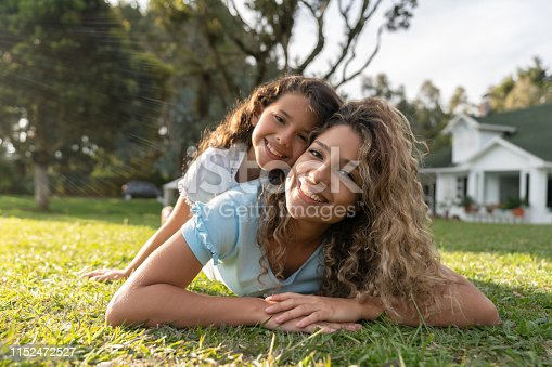Portrait of a happy mother and daughter playing in the backyard of their beautiful house and looking at the camera smiling - real estate concepts