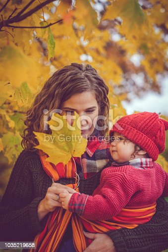 Woman with her baby enjoying autumn outdoors