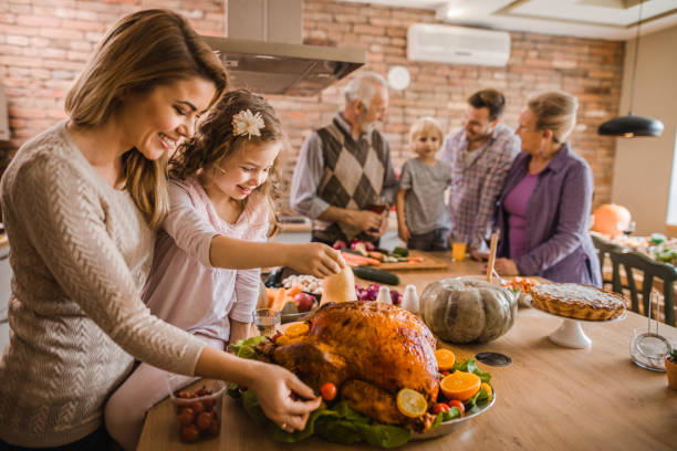 happy mother and daughter preparing roasted turkey for thanksgiving dinner. - family dinner stock photos and pictures