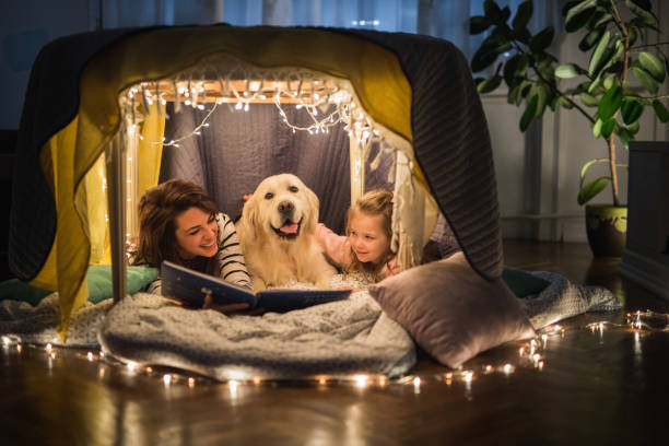happy mother and daughter relaxing with a dog in a tent and reading a book. - canide foto e immagini stock
