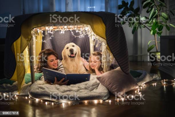 Happy mother and daughter relaxing with a dog in a tent and reading a picture id938027618?b=1&k=6&m=938027618&s=612x612&h=pnxdijh1xqfwmflnt0gfcm4xsfl3oyalc3qszs3ryrk=