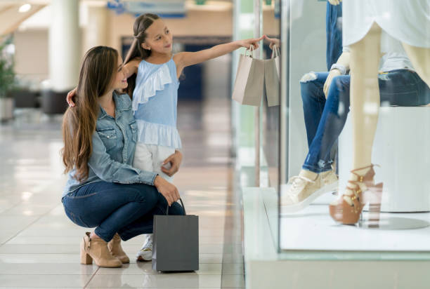 Happy mother and daughter shopping at the mall stock photo