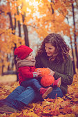 Happy mother and daughter sitting in autumn park