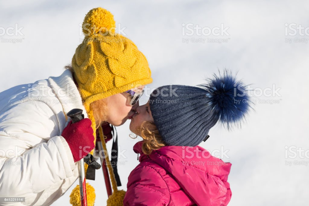 Happy mother and daughter skiers stock photo