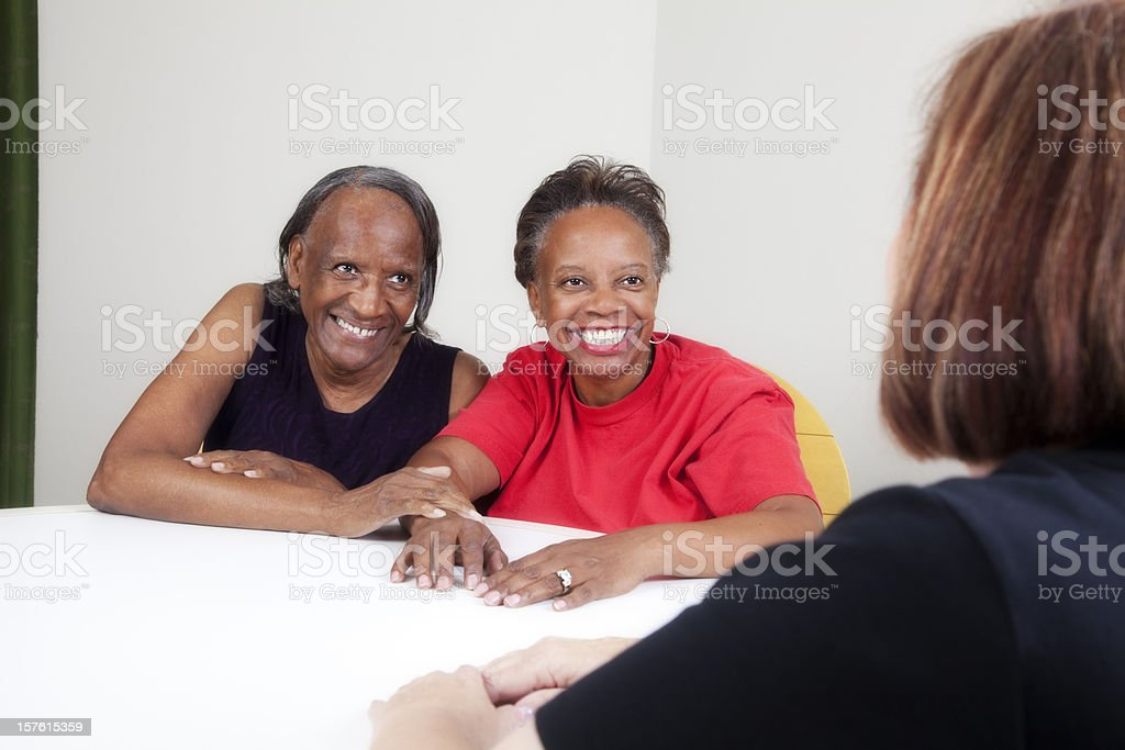 Happy mother and daughter talking with a social worker royalty-free stock photo