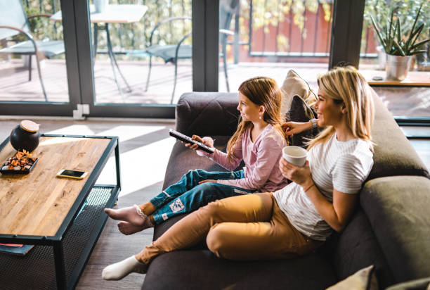 Happy mother and daughter watching TV at home. Young happy mother and her daughter relaxing on sofa in the living room and watching TV. watching tv stock pictures, royalty-free photos & images