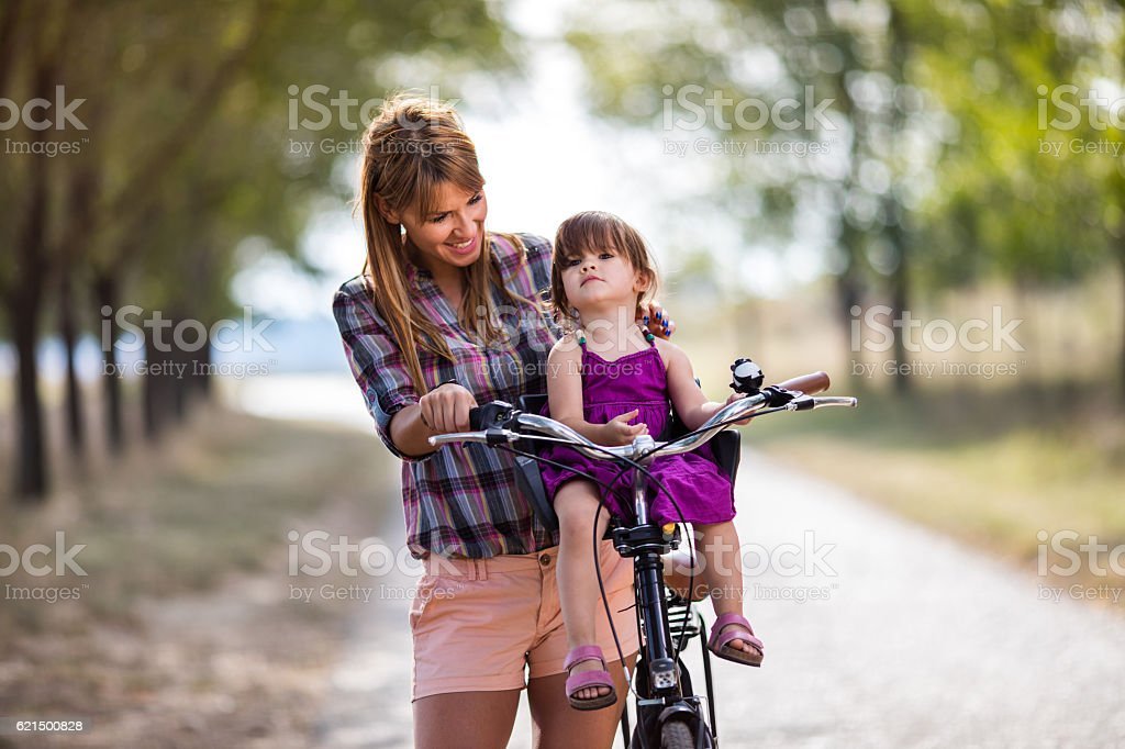 Happy mother and daughter with bicycle spending day outdoors. Lizenzfreies stock-foto