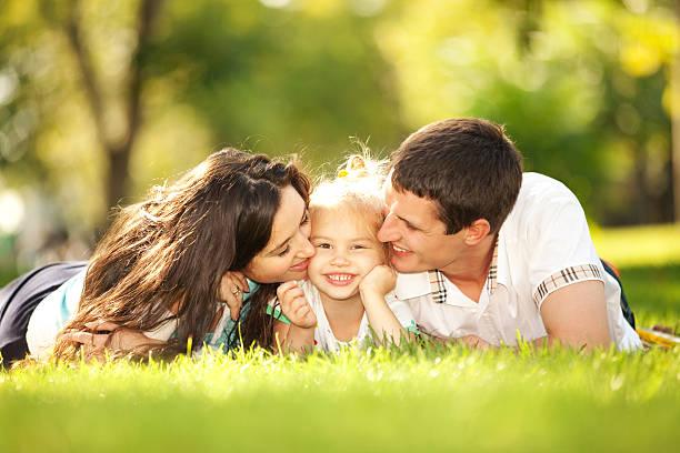 Glückliche Mutter und Vater küsst ihre Tochter im park – Foto