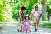 Happy African American mother and father teaching their toddler daughter to ride a tricycle. She is smiling and is wearing a pink helmet. The tricycle is also pink. There are many trees behind them on the path.
