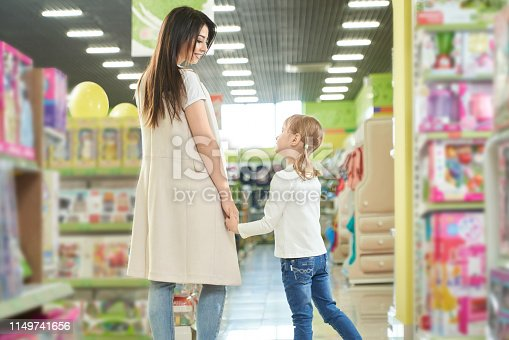 Happy mother brunette and little girl walking, posing in toy store of shopping centre. Big modern department store with many shelves and colorful box with toys.