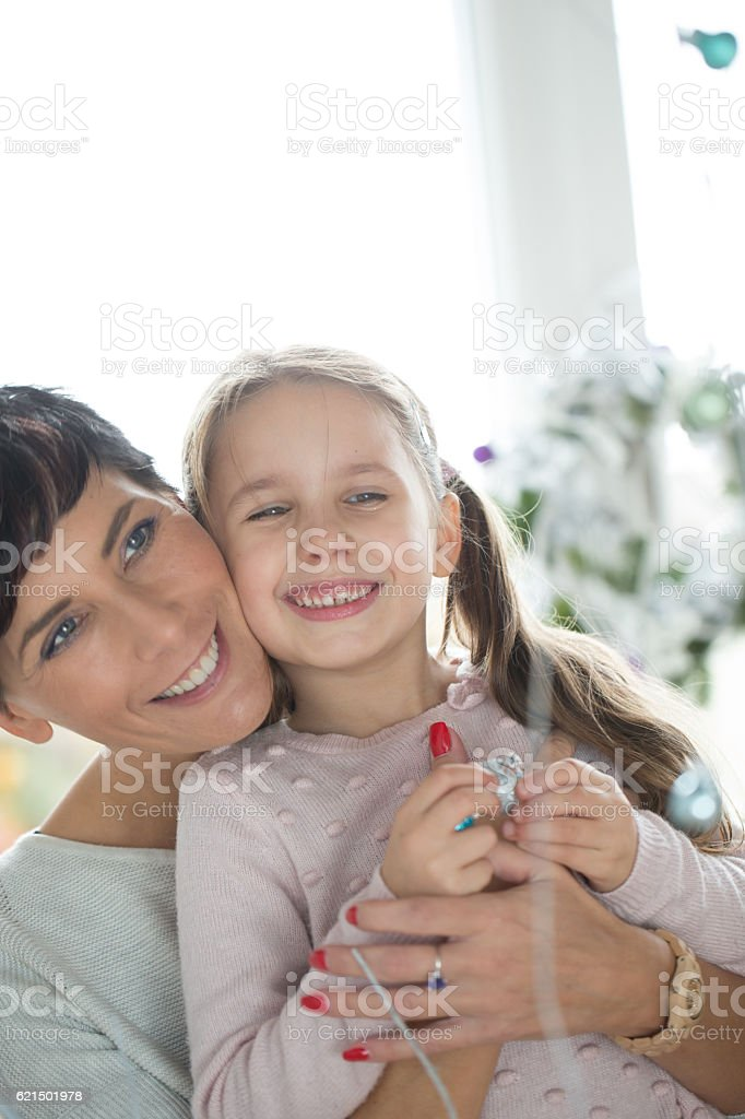 Happy Mother and her Daughter decorating the Christmas Tree Lizenzfreies stock-foto