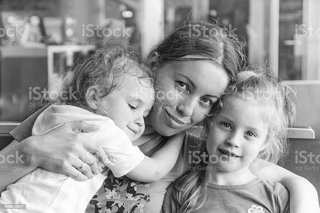 Happy mother and her daughters hug each other stock photo