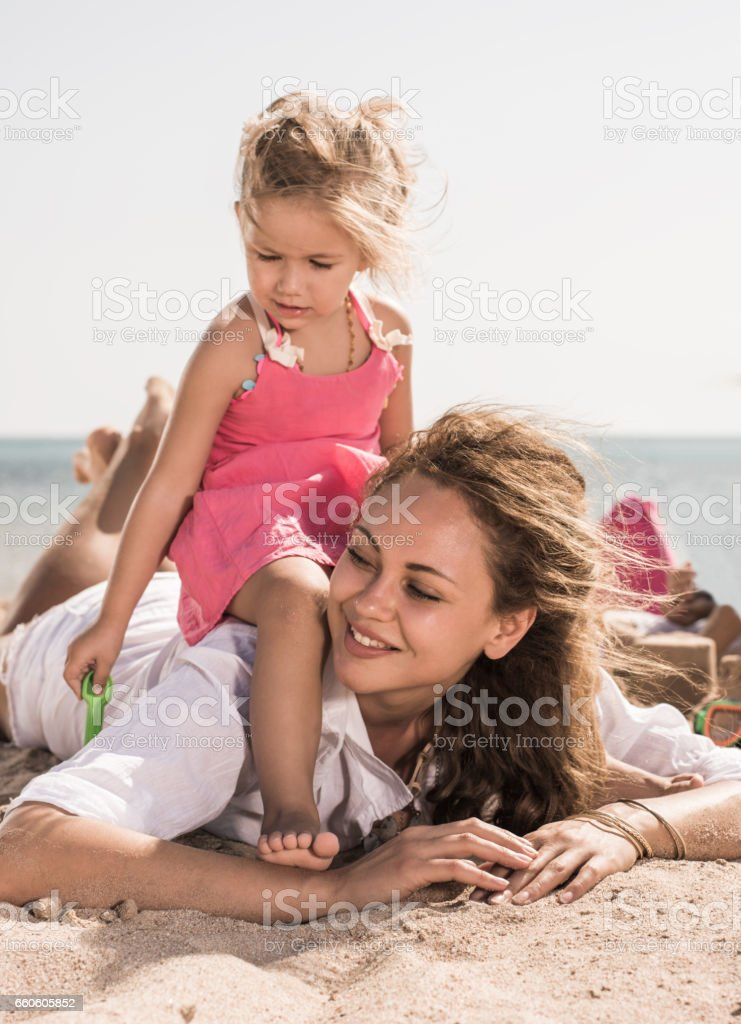 Happy mother and her little girl relaxing in sand. royalty-free stock photo