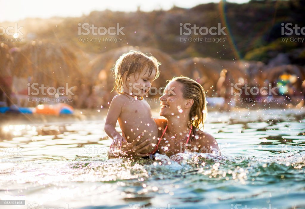 Happy mother and her small boy having fun during summer vacation in the sea. stock photo