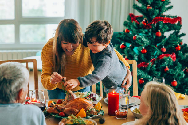 happy mother and her son having fun while holding roasted turkey leg - cena natale foto e immagini stock