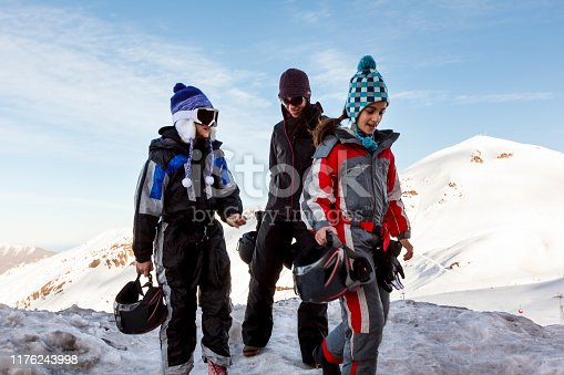 Happy mother and her two young daughters girls wearing ski cloths standing on top of a snow capped mountain
