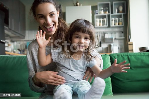 Portrait of happy excited young mother and kid girl waving hands looking at camera, smiling mom with child daughter making video call, family vloggers recording video blog or vlog together concept