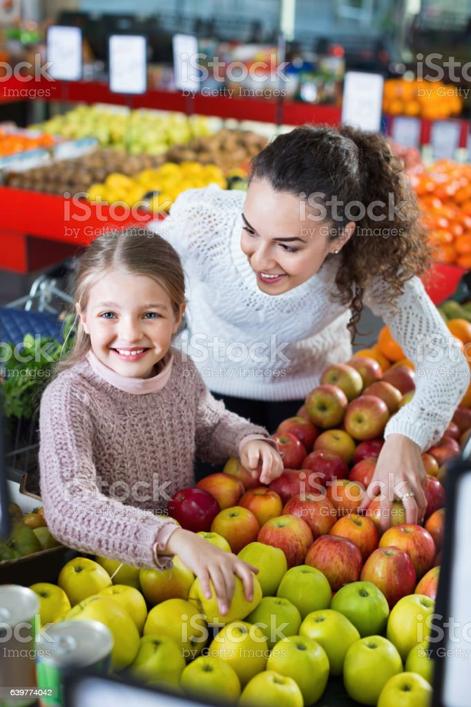 Happy mother and little daughter choosing seasonal fruits stock photo