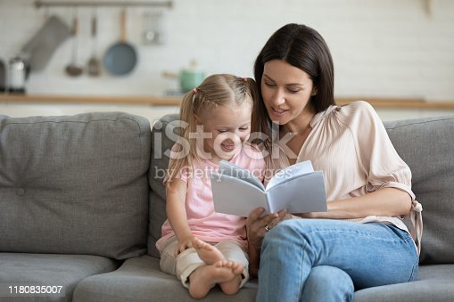 1070262182 istock photo Happy mother and little daughter reading book together at home 1180835007