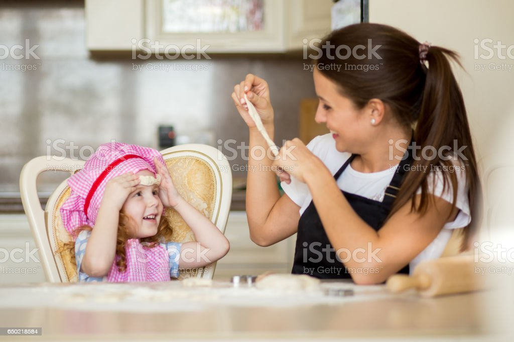 Happy mother and little girl making fun with dough stock photo