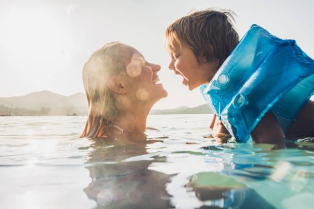 happy mother and son having fun while swimming in sea on summer vacation. - nuoto mare foto e immagini stock